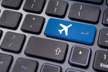 buy online: a plane sign on keyboard, to illustrate online booking or purchase of plane ticket or business travel concepts.