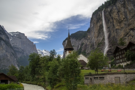 Lauterbrunnen Switzerland with church and waterfall Редакционное