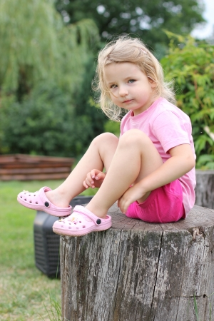 little girl sitting: white girl sitting on a tree stump Stock Photo