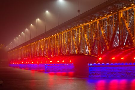 Illuminated bridge in Plock at foggy night, Poland