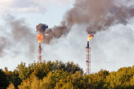 Smoking industrial chimneys, black clouds and flame over forest Standard-Bild - 117531909