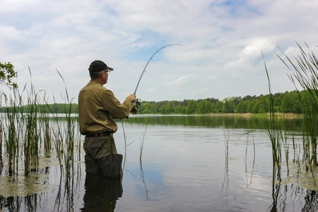 Angler catching the fish in lake