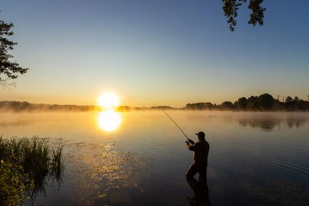 Pêcheur à la ligne attrapant le poisson pendant le lever de soleil