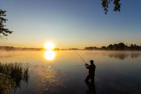 Wędkarz łowi ryby podczas wschodu słońca