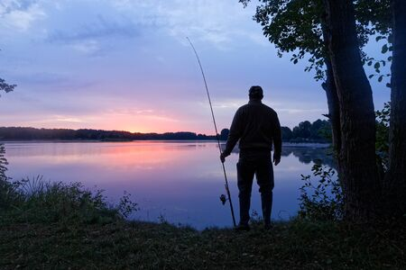 angler standing on the lake shore during sunrise
