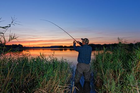 Angler catching the fish during sunset