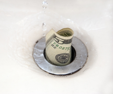 mistake: Five dollar bill going down the drain with water droplets. Room for copy
