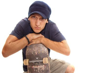 skater posing with his board, resting on one knee Stock Photo - 5440974