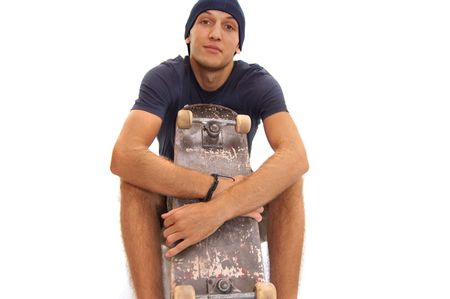 skater with cap sitting with a skate on his knees