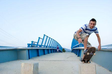 skater performing a lip trick on bridge photo