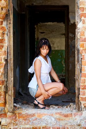 Pretty girl squats in a doorway of ruined structure photo