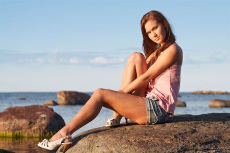 denim shorts: Young girl with beautiful legs sitting on a stone Stock Photo