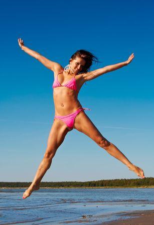 beine spreizen: Frau im rosa Bikini springt hoch auf einen Strand mit einer Hand und die Beine weit verbreitet Lizenzfreie Bilder