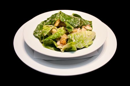 Caesar salad with shrimps on a white plate isolated on black photo