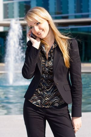 Happy young blond business woman talking on a cell phone photo