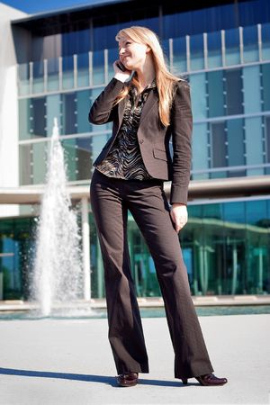 Happy young blond business woman standing near office building and talking on a phone photo
