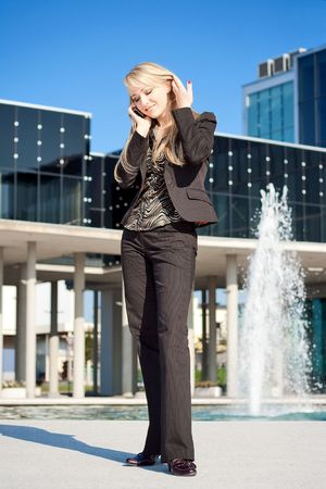 Young blond business woman standing near office building and touching her hair while talking on a phone photo
