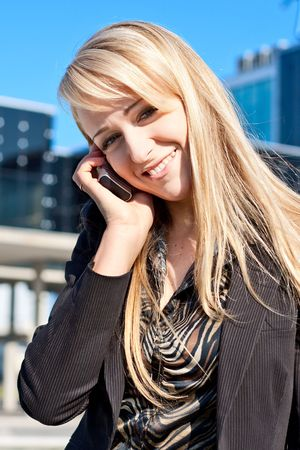 Portrait of a young smiling  business lady talking on a phone photo