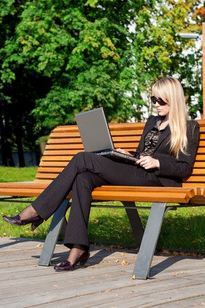Businesswoman in sunglasses sitting on a bench and working on laptop photo