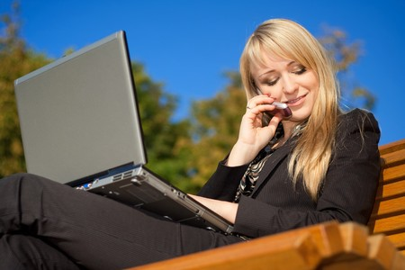 Businesswoman in sunglasses sitting on a bench in park, working on a laptop and talking on a phone photo