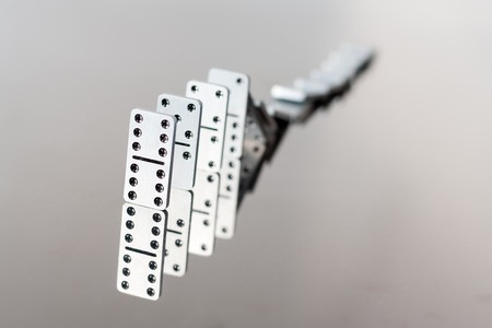 collapsed: A queue of falling steel dominoes with reflection in polished surface