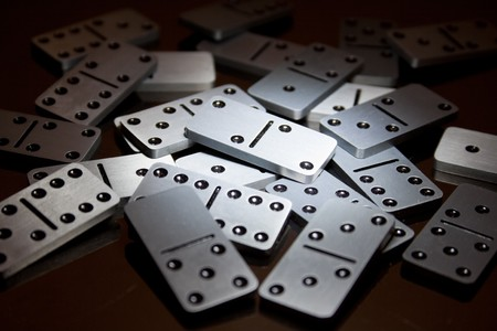 domino effect: Steel dominoes on a polished surface in a spot light