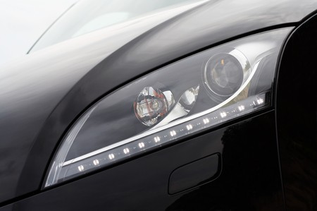 coupe: Headlight detail of a black modern coupe
