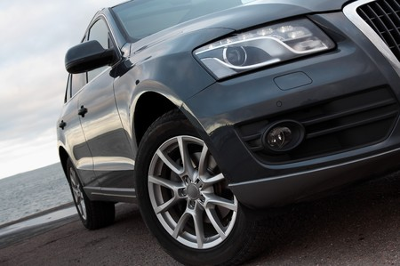 front bumper: Modern SUV headlight and front wheel closeup Stock Photo
