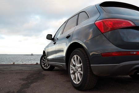 rear wheel: Rear view of a luxury SUV parked near the sea