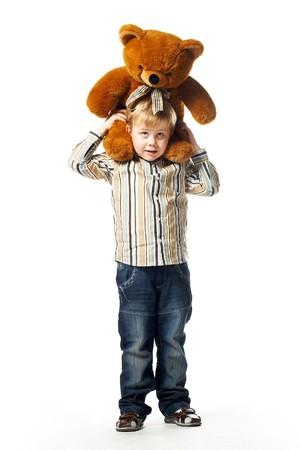 Ni�o de ni�os en edad preescolar de pie con un oso de peluche sobre sus hombros aislados en blanco Foto de archivo - 4426901
