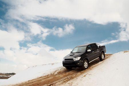 camioneta pick up: Negro camioneta bajar la colina en una carretera de arena