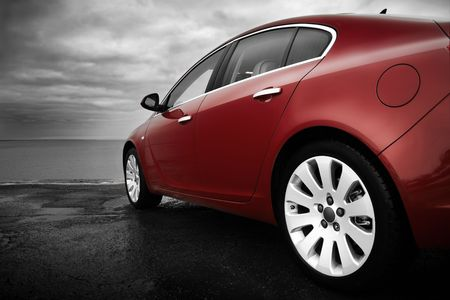 car side: Rear-side view of a luxury cherry red car with monochrome background