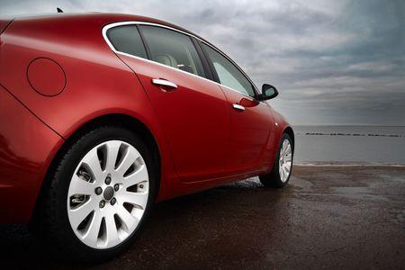 ruedas de coche: La vista lateral trasera de un autom�vil de lujo color rojo cereza con dram�tico cielo
