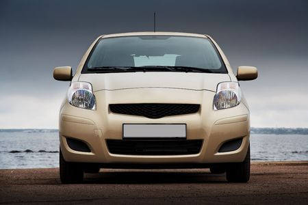 front bumper: Front view of a beige compact hatchback near the sea
