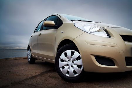 car side: Front-side closeup of a beige compact hatchback near the sea