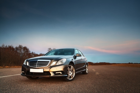 dramatic sky: Modern luxury business sedan in the light of evening sun Editorial