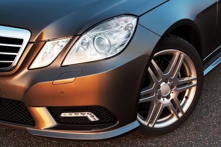 Front wheel, bumper and light detail of a modern sporty luxury car photo