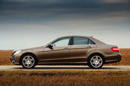 Side view of modern business sedan on a country road Editorial