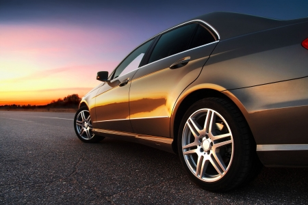 ruedas de coche: La vista lateral trasera de un coche de lujo en la puesta de sol Editorial