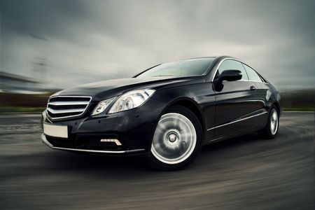 car wheels: Front view of black luxury coupe driving fast