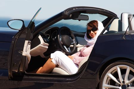 Young lady in sunglasses and headscarf sitting in cabriolet Stock Photo - 5015428