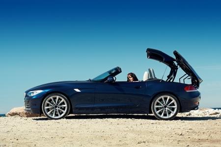 Roadster blu su una giornata di sole, con un tetto a soffietto e una ragazza seduta in macchina