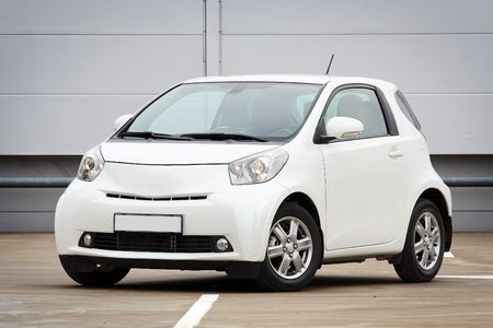 new car lot: 34 front view of ultra compact city car on a parking lot Editorial