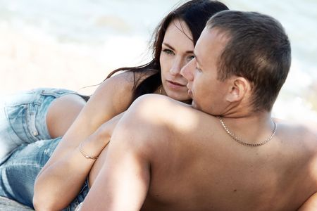 Sensual couple in jeans on a beach photo