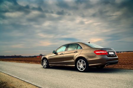 sedan: Rear view of a luxury car on country road with dramatic sky