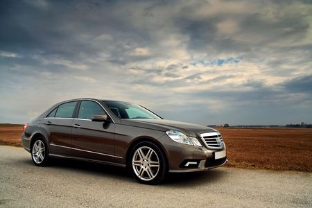 sedan: Front view of a luxury car on country road with dramatic sky