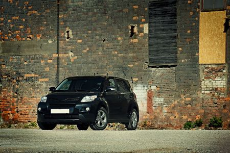 crossover: 34 view of modern crossover vehicle near old brick wall Editorial
