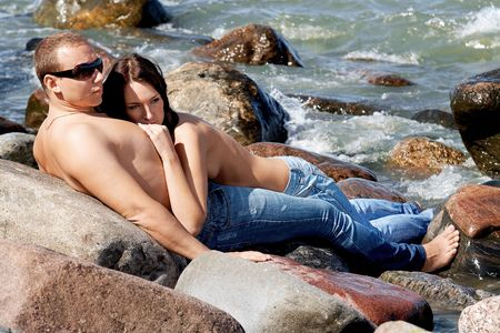 Sensual couple in jeans on a coastline photo