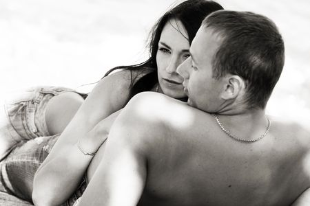 Sensual couple in jeans on a beach in monochrome photo
