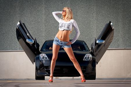 Sexy babe standing in front of tuned supercar Stock Photo - 5429890